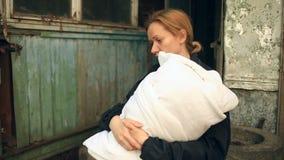 Εξαντλημένη γυναίκα, μητέρα με ένα νήπιο στα όπλα της στο υπόβαθρο των βομβαρδισμένων σπιτιών Πόλεμος, σεισμός, πυρκαγιά απόθεμα βίντεο