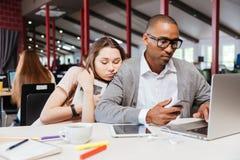 Εξαντλημένοι επιχειρηματίες που κοιμούνται και που εργάζονται στην αρχή Στοκ Εικόνες