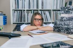 Εξαντλημένος γραμματέας με το σωρό φακέλλων στον υπολογιστή γραφείου Στοκ φωτογραφία με δικαίωμα ελεύθερης χρήσης