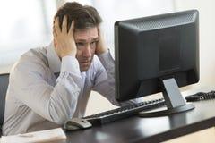 Εξαντλημένος επιχειρηματίας που εξετάζει το όργανο ελέγχου υπολογιστών Στοκ Εικόνες