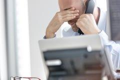 Εξαντλημένος επιχειρηματίας που χρησιμοποιεί το τηλέφωνο γραμμών εδάφους στην αρχή Στοκ εικόνες με δικαίωμα ελεύθερης χρήσης