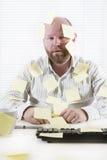 Εξαντλημένος εργαζόμενος γραφείων με τις σημειώσεις παντού Στοκ Εικόνες
