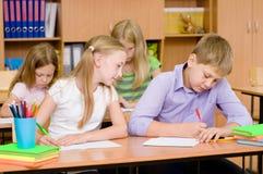Εξαπάτηση μαθητριών στο διαγωνισμό, που εξετάζει το γράψιμο ενός φίλου Στοκ φωτογραφία με δικαίωμα ελεύθερης χρήσης