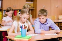 Εξαπάτηση μαθητών στο διαγωνισμό, που εξετάζει το γράψιμο ενός φίλου Στοκ φωτογραφία με δικαίωμα ελεύθερης χρήσης