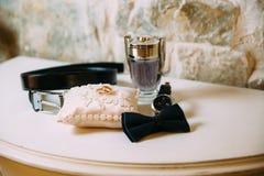 Εξαρτήματα ατόμων, ζώνη δέρματος, άρωμα, δεσμός τόξων, χρυσές δαχτυλίδια του νεόνυμφου, ρολόγια και νύφες σε έναν άσπρο πίνακα στοκ φωτογραφίες