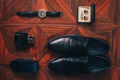 Εξαρτήματα ατόμων: ρολόι, δεσμός, ζώνη, μανικετόκουμπα, τοπ άποψη παπουτσιών αρώματος στοκ εικόνες
