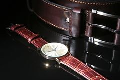 Εξαρτήματα ατόμων ` s με το καφετί πορτοφόλι, τη ζώνη και το ρολόι δέρματος στο μαύρο υπόβαθρο καθρεφτών Στοκ Φωτογραφία