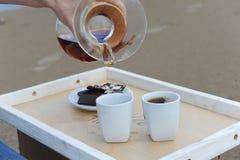 Εξαρτήματα για τον εναλλακτικό καφέ παρασκευής σε έναν δίσκο στην αμμώδη παραλία Καφές χυσιμάτων Barista στα φλυτζάνια στοκ εικόνες