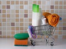 Εξαρτήματα για το πλυντήριο και την καθαρότητα - σαπούνι, σαμπουάν, πετσέτα στο καλάθι αγορών στοκ εικόνα