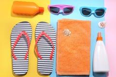 Εξαρτήματα παραλιών Διάφορα κρέμες, γυαλιά, καπέλο και πετσέτα με τα κοχύλια θάλασσας σε ένα χρωματισμένο υπόβαθρο Επίπεδος βάλτε στοκ φωτογραφία με δικαίωμα ελεύθερης χρήσης