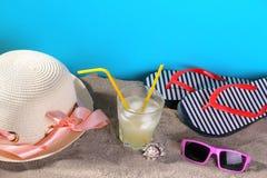 Εξαρτήματα παραλιών με την κρύα λεμονάδα Καπέλο, σαγιονάρες και γυαλιά στην άμμο σε ένα μπλε υπόβαθρο στοκ φωτογραφίες