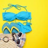 Εξαρτήματα παραλιών στο κίτρινο υπόβαθρο - γυαλιά ηλίου, μπικίνι, σαγιονάρες και ριγωτό καπέλο Το καλοκαίρι είναι ερχόμενη έννοια στοκ εικόνα