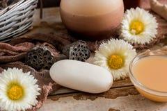 Εξαρτήματα SPA με το σαπούνι, κύπελλο με τα ξηρά chamomile λουλούδια, κομμάτι Α του άσπρου σαπουνιού, υγρό καφετί σαπούνι, κοχύλι Στοκ Φωτογραφία