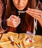 Εξαρτημένος κοριτσιών με το κουτάλι και τον αναπτήρα ηρωίνης στοκ φωτογραφίες