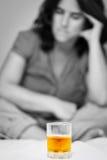 Εξαρτημένος οινοπνεύματος που εξετάζει ένα ποτήρι του ουίσκυ στοκ εικόνες