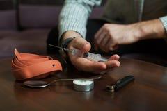 Εξαρτημένος που προετοιμάζει μια δόση της ηρωίνης για την έγχυση στοκ φωτογραφία με δικαίωμα ελεύθερης χρήσης