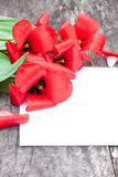 Εξασθενισμένες κόκκινες τουλίπες στο δρύινο καφετή πίνακα με το άσπρο φύλλο του pape Στοκ φωτογραφία με δικαίωμα ελεύθερης χρήσης