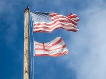 Εξασθενισμένος και φορεμένος κάτοικος της Χαβάης και αμερικανικές σημαίες σε ένα ξύλινο κοντάρι σημαίας στοκ εικόνες