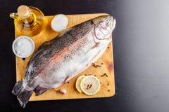 Εξεντερισμένη πέστροφα σε έναν ξύλινο τέμνοντα πίνακα με τα συστατικά για το μαγείρεμα Τοπ όψη Στοκ Εικόνα