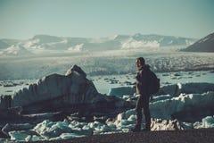 Εξερευνητής γυναικών lookig στη λιμνοθάλασσα Jokulsarlon, Ισλανδία Στοκ Εικόνες
