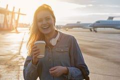 Εξερχόμενο θηλυκό δοκιμάζοντας ποτό υπαίθριο στον αερολιμένα Στοκ Εικόνες