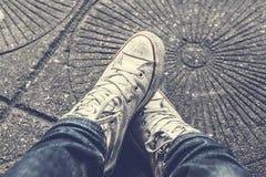 Εξετάζοντας κάτω τα παπούτσια, πόδια ατόμων ` s στο τζιν παντελόνι Στοκ εικόνα με δικαίωμα ελεύθερης χρήσης