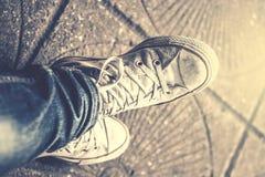 Εξετάζοντας κάτω τα παπούτσια, πόδια ατόμων ` s στο τζιν παντελόνι Στοκ φωτογραφία με δικαίωμα ελεύθερης χρήσης