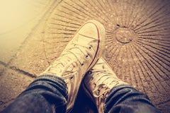 Εξετάζοντας κάτω τα παπούτσια, πόδια ατόμων ` s στο τζιν παντελόνι Στοκ Φωτογραφία