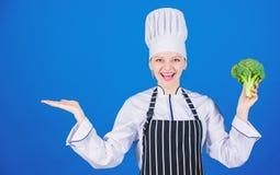 Εξετάστε αυτό Γυναικείος μάγειρας που χαμογελά με το μπρόκολο βιταμινών gesturing μακριά Ευτυχής γυναίκα που διαφημίζει τη φρέσκι στοκ εικόνα