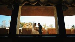 Εξετάστε μέσω του παραθύρου το όμορφο ελκυστικό ζεύγος των newlyweds που κρατούν τα χέρια και που φιλούν tenderly απόθεμα βίντεο