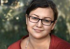 Εξετάστε τη ζωή Ένα νέο κορίτσι εξετάζει μας ενάντια στο backgroun της πρασινάδας και του φωτός του ήλιου Στοκ φωτογραφία με δικαίωμα ελεύθερης χρήσης