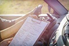 Εξεταστής που συμπληρώνει τη μορφή οδικής δοκιμής αδειών οδηγών ` s Στοκ φωτογραφία με δικαίωμα ελεύθερης χρήσης