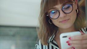 Εξευγενίστε και νέο κορίτσι, που χαμογελά, κοιτάζοντας μακριά και σε ένα smartphone απόθεμα βίντεο