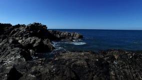 Εξευγενίστε το ανοδικό τηγάνι κινήσεων πέρα από τον παράκτιο βράχο για να αποκαλύψετε τον ορίζοντα της μπλε θάλασσας και του ουρα φιλμ μικρού μήκους