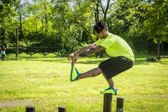 Εξισορρόπηση αθλητικών τύπων στη στάση οκλαδόν πιστολιών στον ξύλινο φραγμό Στοκ εικόνες με δικαίωμα ελεύθερης χρήσης