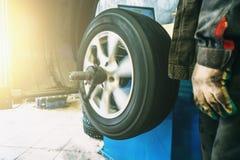 Εξισορρόπηση ροδών ή επισκευή και ρόδα αυτοκινήτων αλλαγής στο αυτόματο γκαράζ υπηρεσιών ή εργαστήριο από το μηχανικό Στοκ Εικόνες