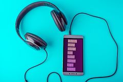 Εξισωτής στην οθόνη του τηλεφώνου με τα ακουστικά που παίζουν τη μουσική σε ένα μπλε υπόβαθρο Στοκ φωτογραφία με δικαίωμα ελεύθερης χρήσης