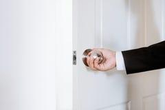 Εξογκωμάτων πορτών εκμετάλλευσης χεριών επιχειρηματιών ανοίγματος ή κλεισίματος πόρτα, με φωτεινό πίσω από την πόρτα Στοκ φωτογραφία με δικαίωμα ελεύθερης χρήσης