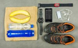 Εξοπλισμός για μια κατάρτιση δρομέων Εξάρτηση μέτρησης σφυγμού - ένα όργανο ελέγχου Garmin, ένα isotonic ποτό, μπανάνες, μια πετσ Στοκ εικόνα με δικαίωμα ελεύθερης χρήσης