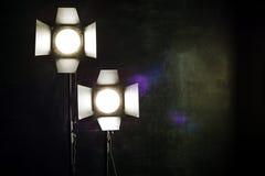 Εξοπλισμός φωτισμού σε έναν μαύρο παλαιό shabby τοίχο υποβάθρου Στοκ Φωτογραφίες