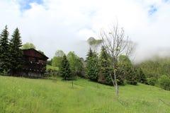 Εξοχικό σπίτι βουνών σε έναν ομιχλώδη καιρό Στοκ Εικόνα