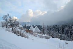 Εξοχικό σπίτι βουνών το χειμώνα, το δάσος πεύκων, τον ουρανό και τα σύννεφα Στοκ Εικόνα