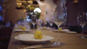 Εξυπηρέτηση ενός πίνακα σε ένα ακριβό εστιατόριο Κενά γυαλιά κρασιού, άσπρα πιάτα, μαχαιροπήρουνα σε έναν ξύλινο πίνακα juicy λεμ φιλμ μικρού μήκους