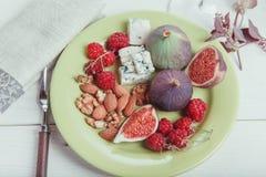 Εξυπηρέτηση του πίνακα, φρέσκα σύκα, φρούτα, μούρα, τυρί, καρύδια σε ένα άσπρο ξύλινο υπόβαθρο Στοκ εικόνες με δικαίωμα ελεύθερης χρήσης