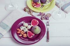 Εξυπηρέτηση του πίνακα, φρέσκα σύκα, φρούτα, μούρα, τυρί, καρύδια σε ένα άσπρο ξύλινο υπόβαθρο Στοκ Εικόνες