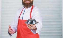 Εξυπηρετήστε τα τρόφιμα r το άτομο κρατά το δίσκο πιάτων κουζινών στο εστιατόριο o u στοκ εικόνα με δικαίωμα ελεύθερης χρήσης