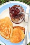 Εξυπηρετήστε τις τηγανίτες με τη μαρμελάδα σε ένα πιάτο για το πρόγευμα Στοκ Εικόνες
