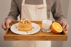 Εξυπηρετήστε τις τηγανίτες μπανανών προγευμάτων με το μέλι και τα καρύδια στοκ εικόνες