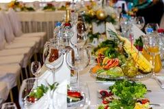 Εξυπηρετούμενα πιάτα στον πίνακα για τις διακοπές Μαχαιροπήρουνα και τρόφιμα στα άσπρα τραπεζομάντιλα στο εστιατόριο Σχεδιάστε έν στοκ φωτογραφία