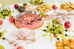 Εξυπηρετούμενοι πίνακες στο συμπόσιο Επιδόρπια, φρούτα και ζύμες στον μπουφέ catering στοκ φωτογραφία